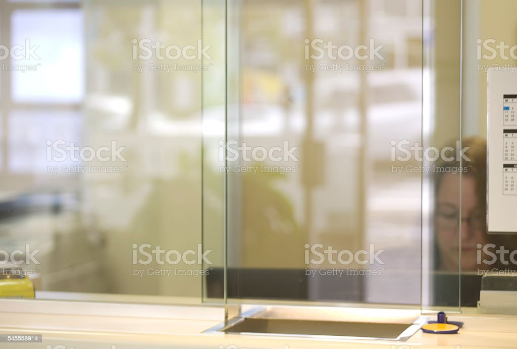 Woman works in office viewed through glass stock photo