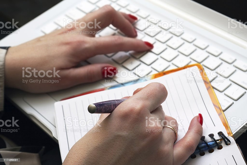 Woman works on a white laptop. stock photo