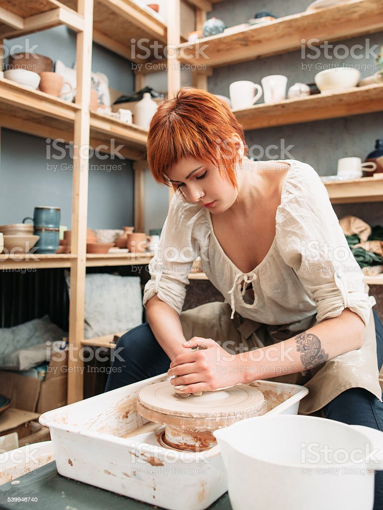 Woman works on potters wheel stock photo