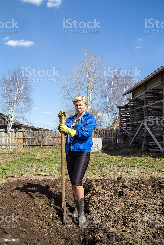 Woman works with spade in spring garden stock photo