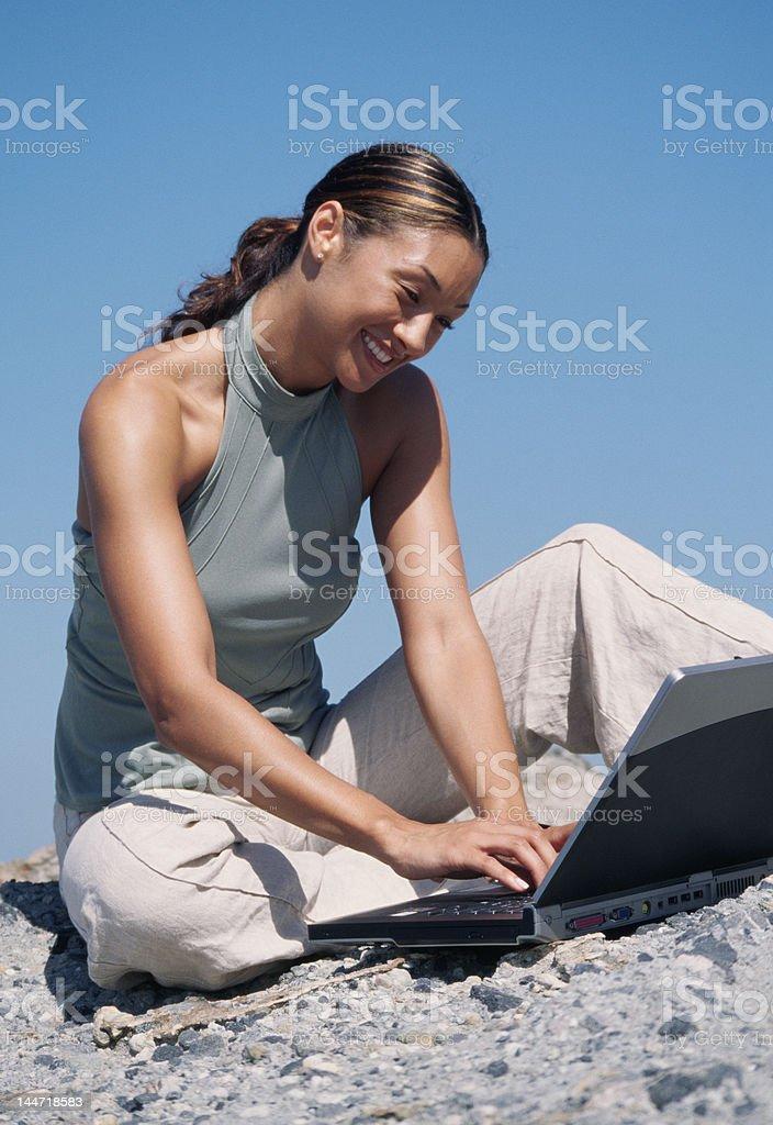 Femme travaille avec un ordinateur portable sur la plage sans fil photo libre de droits