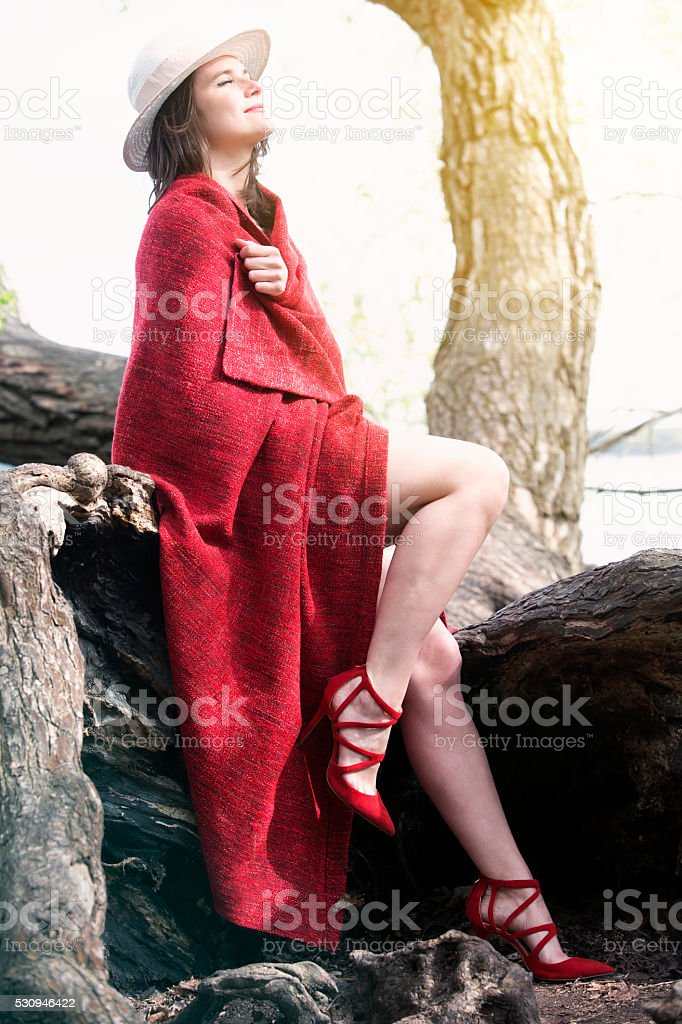 woman wrapped in a blanket sitting on tree stock photo