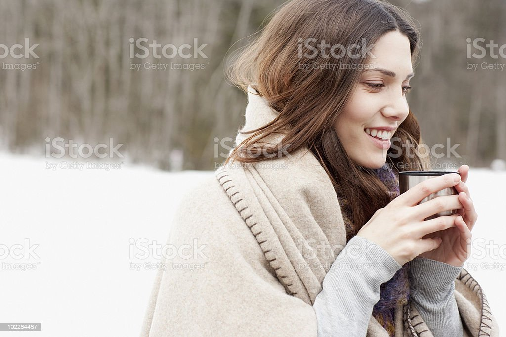 Woman wrapped in blanket drinking coffee royalty-free stock photo