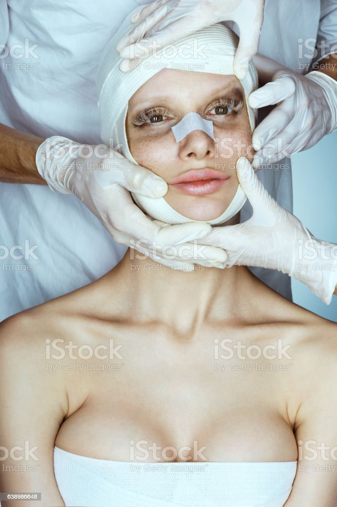 Woman wrapped in medical bandages after facelift. stock photo