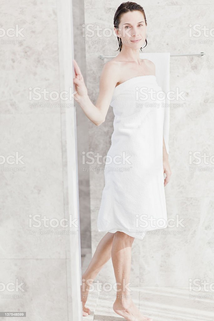 Woman wrapped in towel in bathroom  stock photo