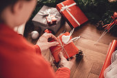 Woman Wrapping Christmas Gifts At Home