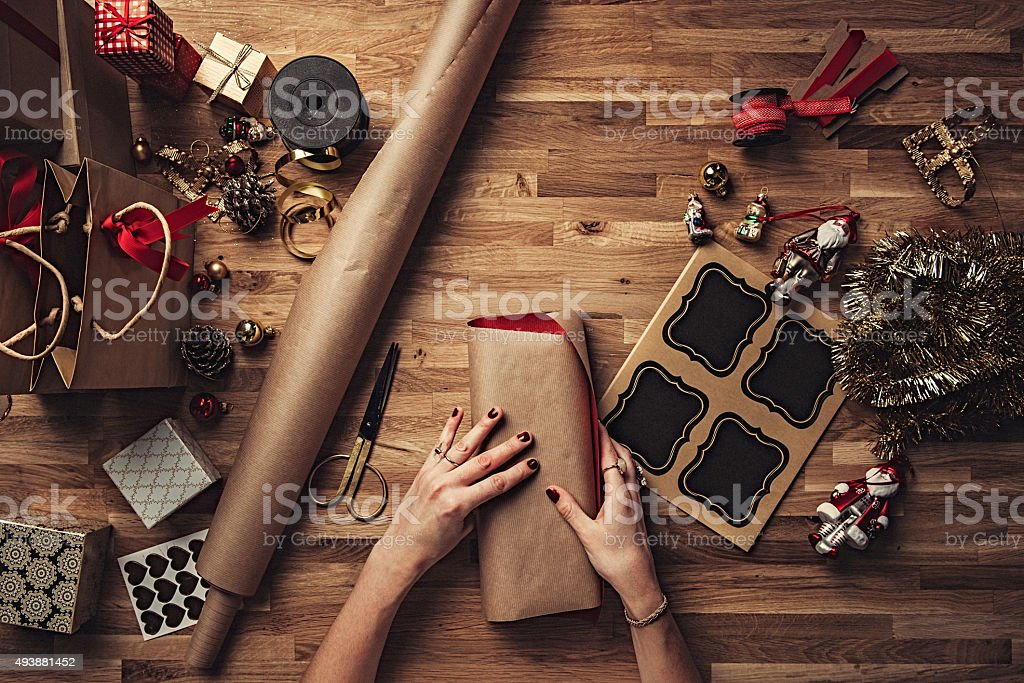 Woman wrapping christmas gifts overhead stock photo