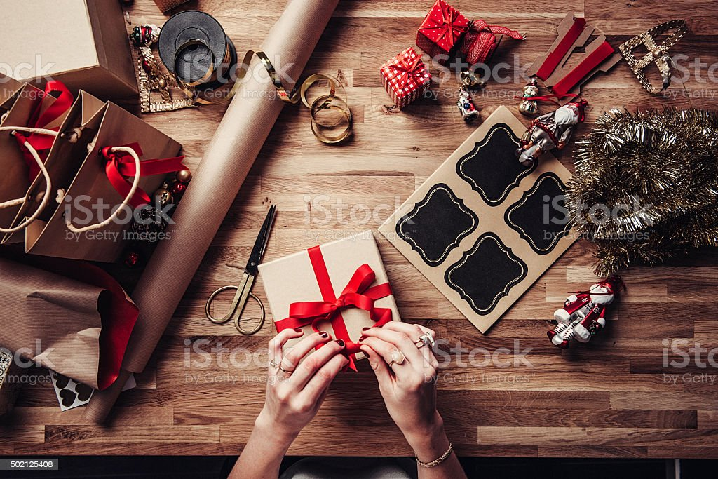 Woman wrapping christmas gifts overhead stock photo
