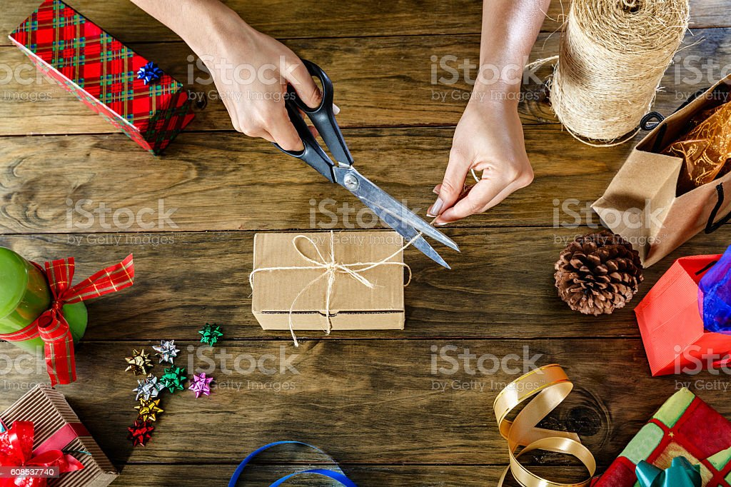 Woman wrapping christmas gifts overhead view stock photo