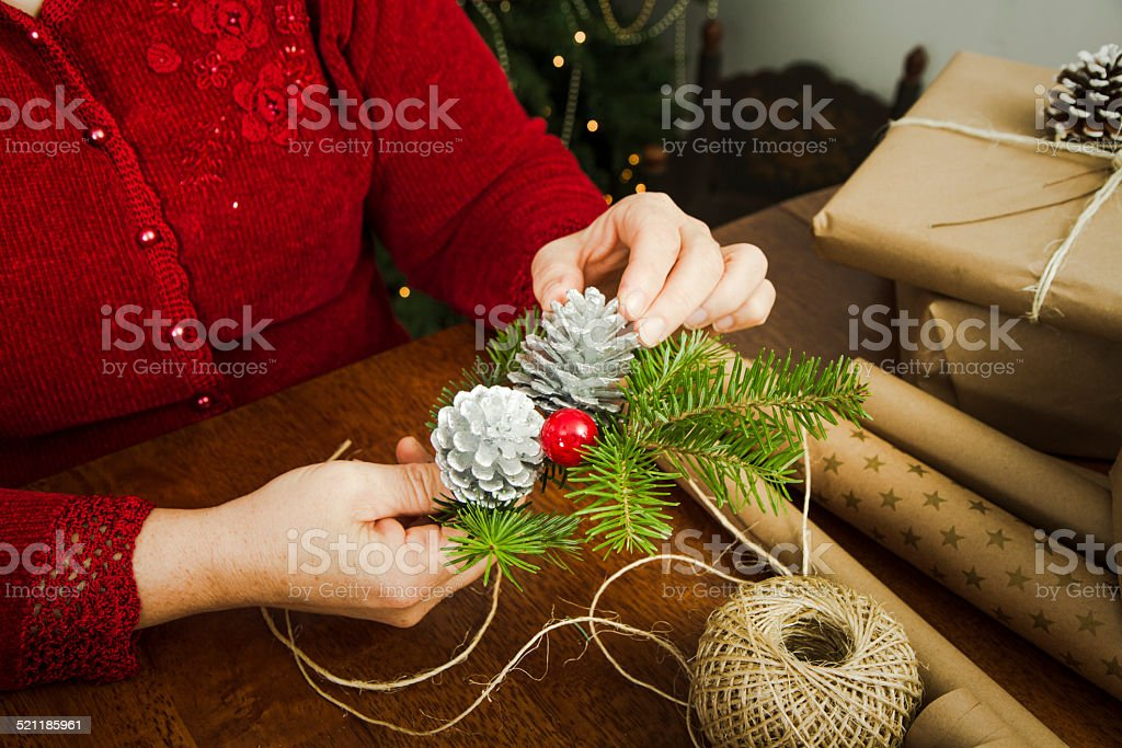 Woman Wrapping Christmas Gifts With Brown Paper & twine