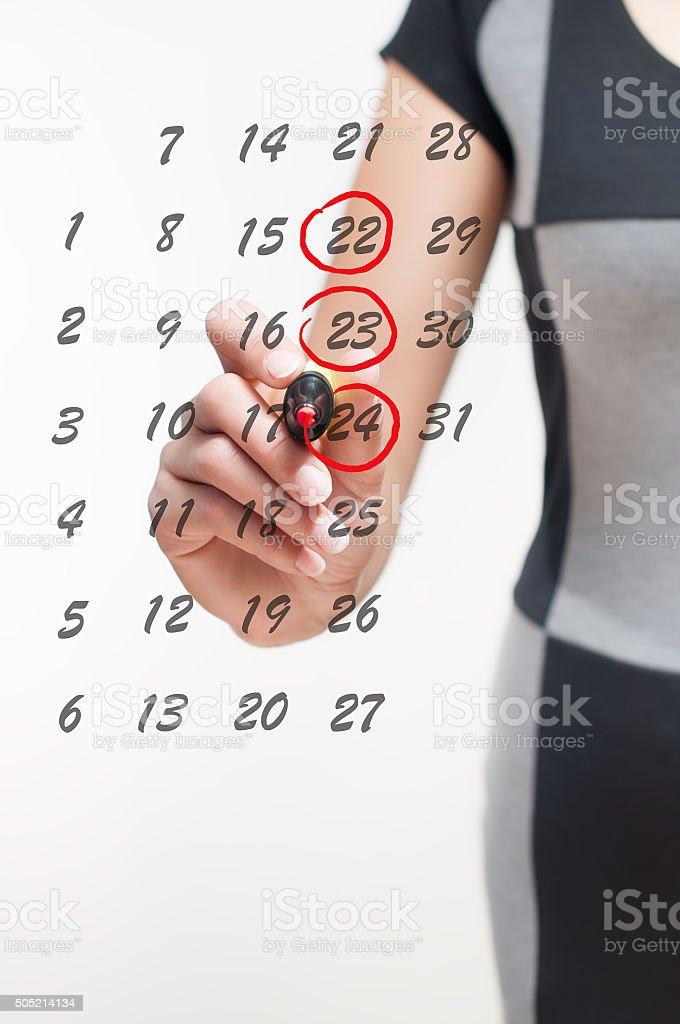 woman writes the days on the calendar stock photo