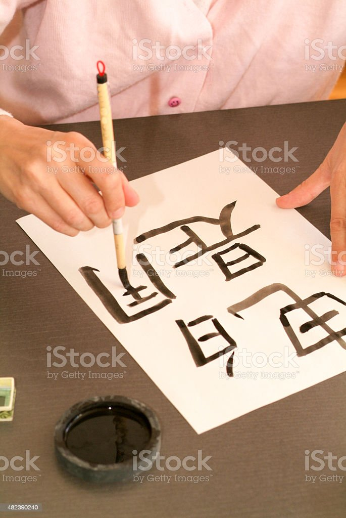 Woman writing Chinese characters stock photo