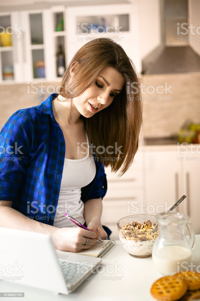 Woman writing down recipe from internet stock photo