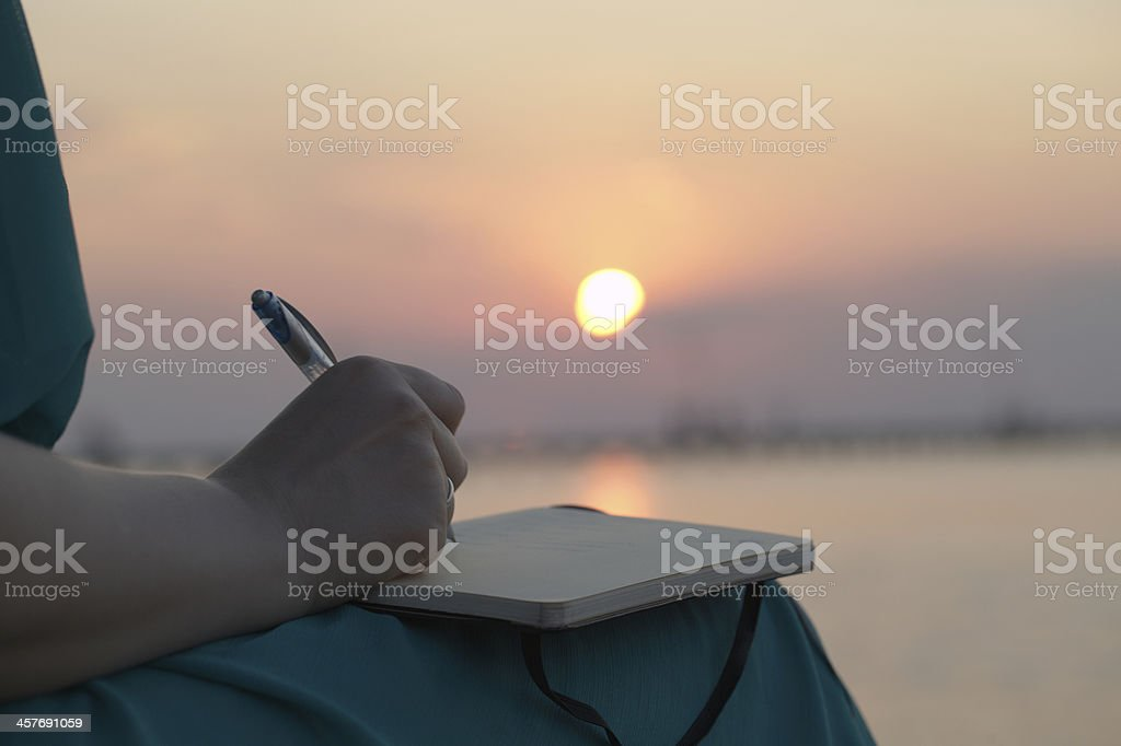 Woman writing in her diary at sunset stock photo