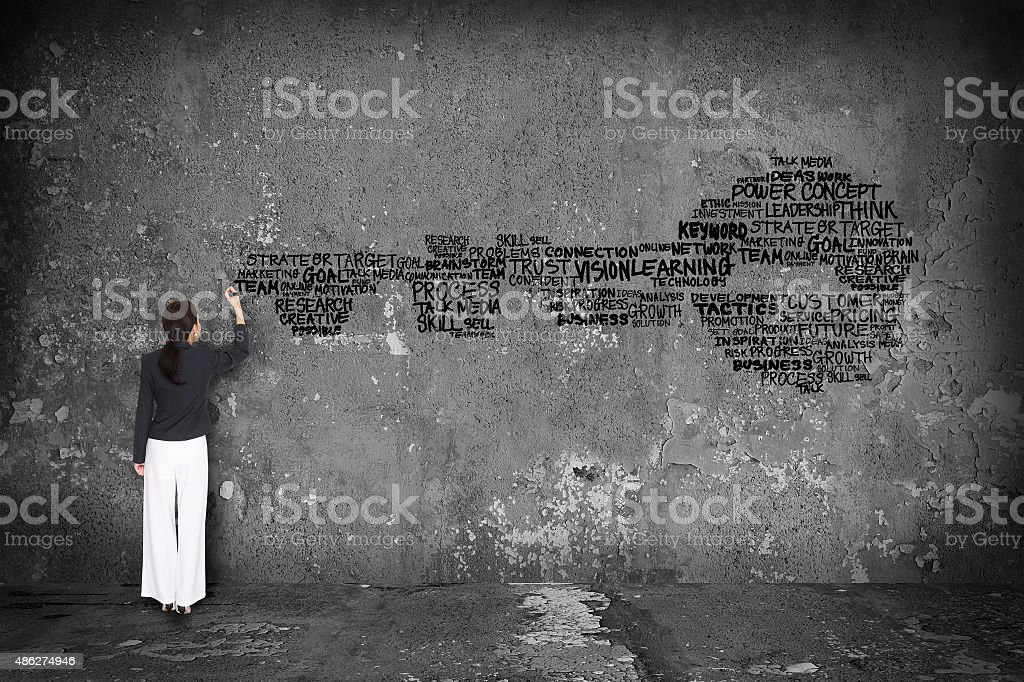 woman writing key with word on wall stock photo