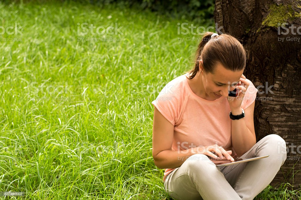 Woman writing message on tablet stock photo