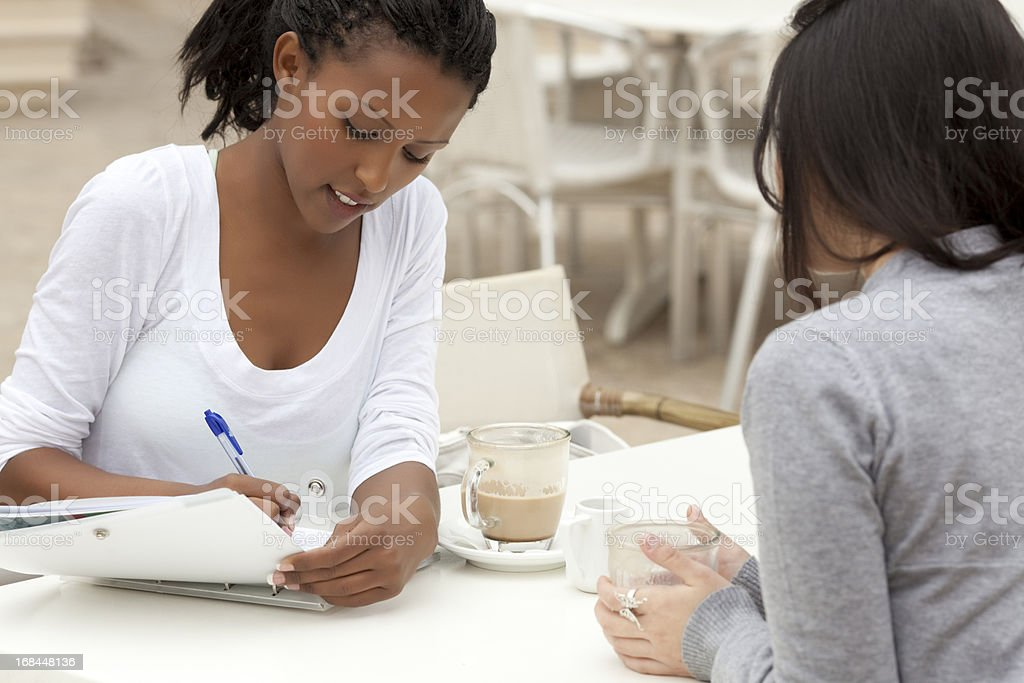 Woman writing on a notebook during a cafe meeting royalty-free stock photo