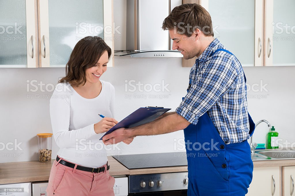 Woman Writing On Clipboard In Front Of Plumber stock photo