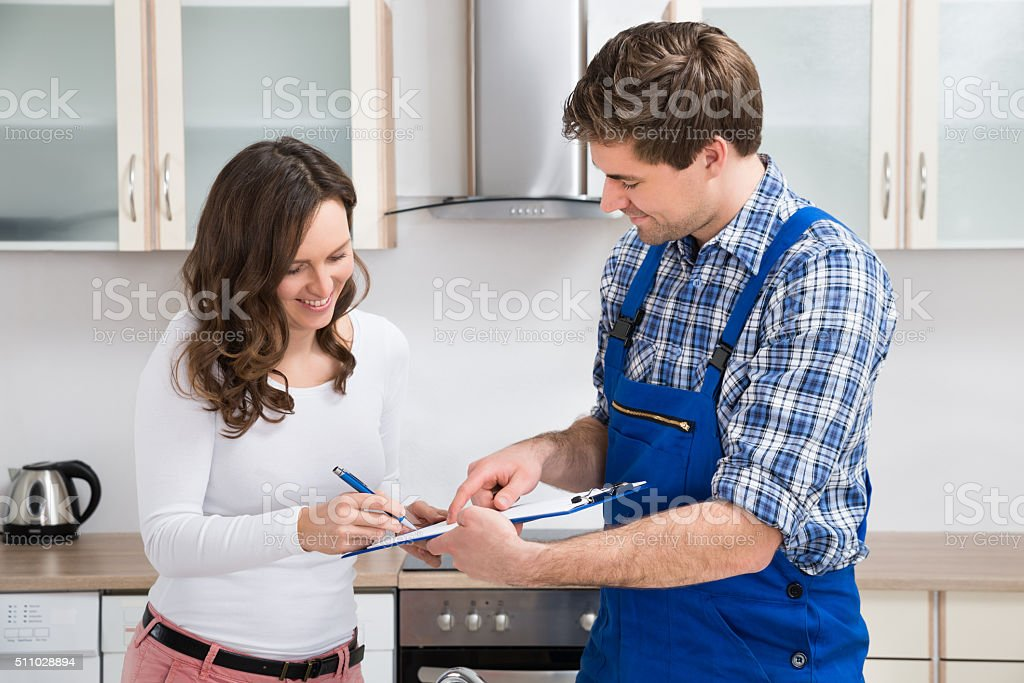 Woman Writing On Clipboard With Plumber In Kitchen Room stock photo