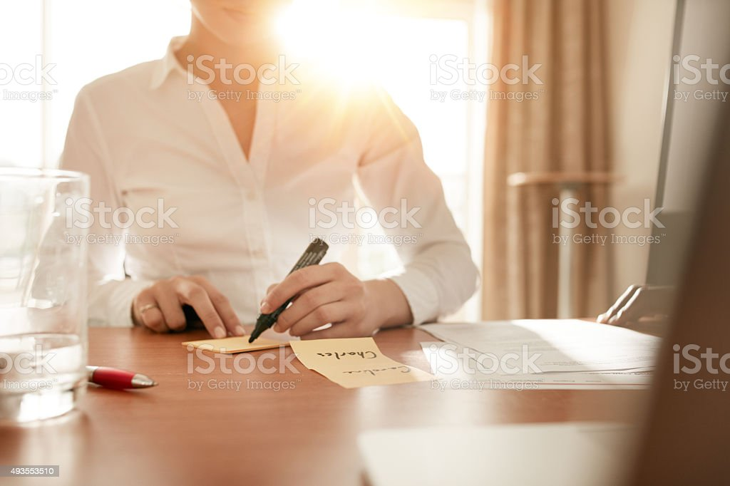 Woman writing on sticky notes at conference room stock photo