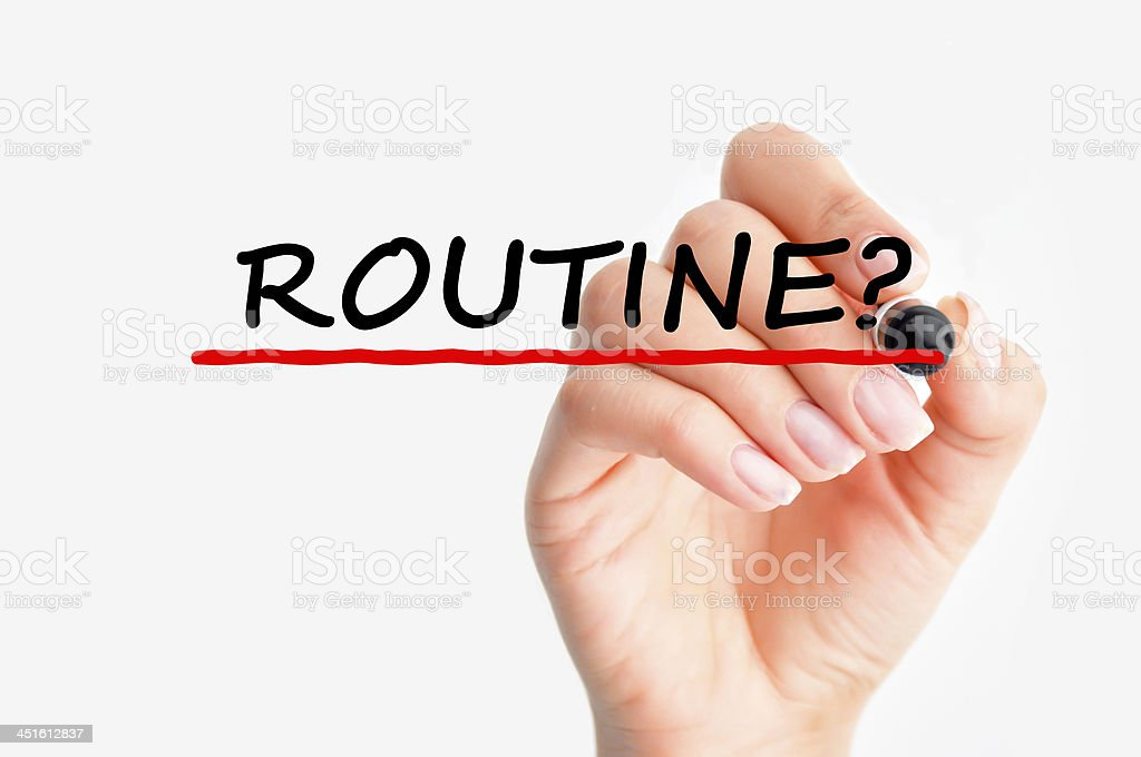 Woman writing 'routine' in black ink stock photo