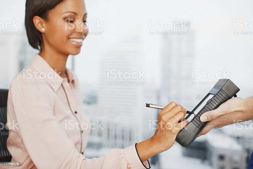 Woman writing signature on electronic device royalty-free stock photo