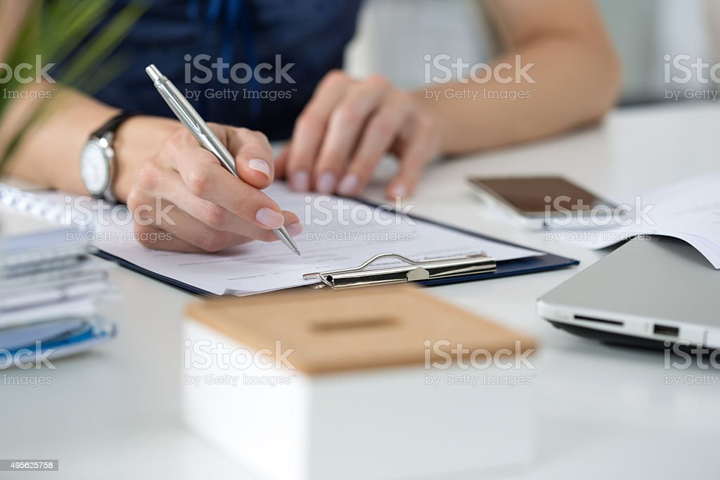 Woman writing something  sitting at her office stock photo