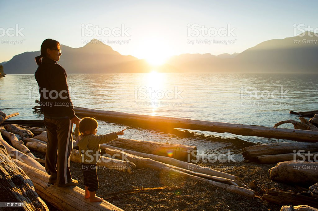 Woman w/small child pointing out to body of water at sunset stock photo