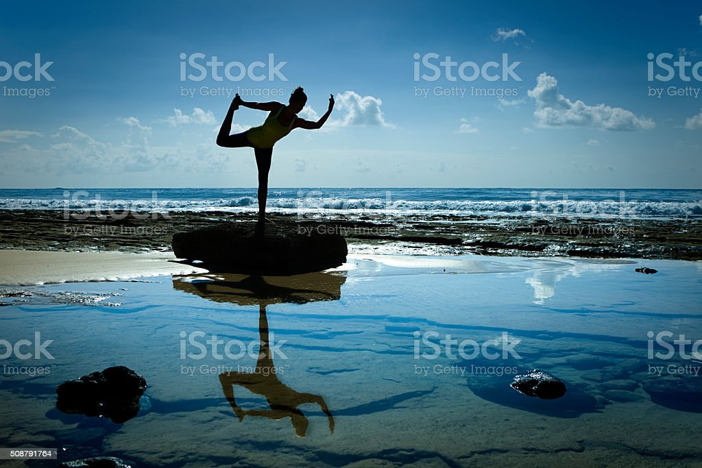 Woman Yoga Exercise in Nature with Sea and Sky Background stock photo