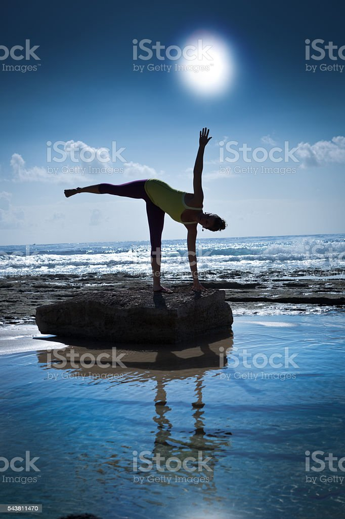 Woman Yoga Exercise in Nature with Sea and Sun Background stock photo