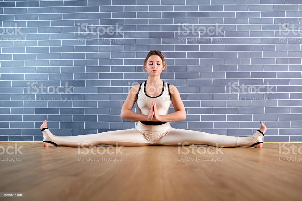 Woman yoga on the splits in gym a gray background stock photo