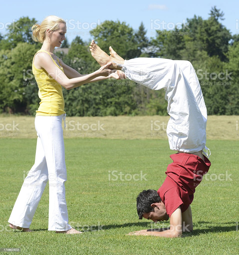 woman yoga trainer helping man with scorpion royalty-free stock photo