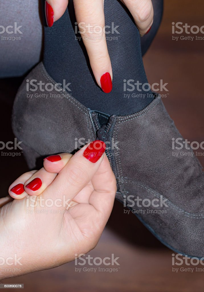 Woman zipping up her suede high heel ankle  boot stock photo