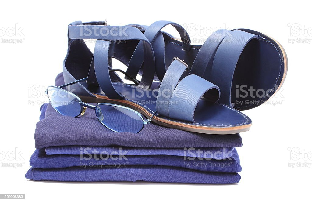 Womanly sandals and sunglasses on pile of blue clothes stock photo