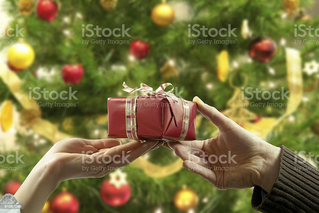 Woman's and man's hand holding, passing red gift, Christmas tree stock photo
