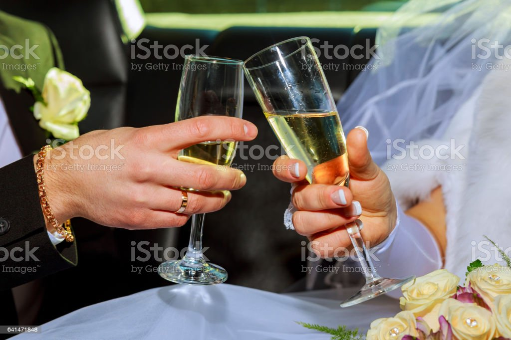 Womans and mans wedding hands with glasses. stock photo