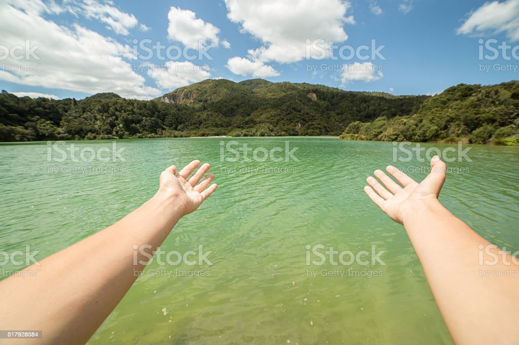Woman's arms stretch towards a green lake in New Zealand stock photo