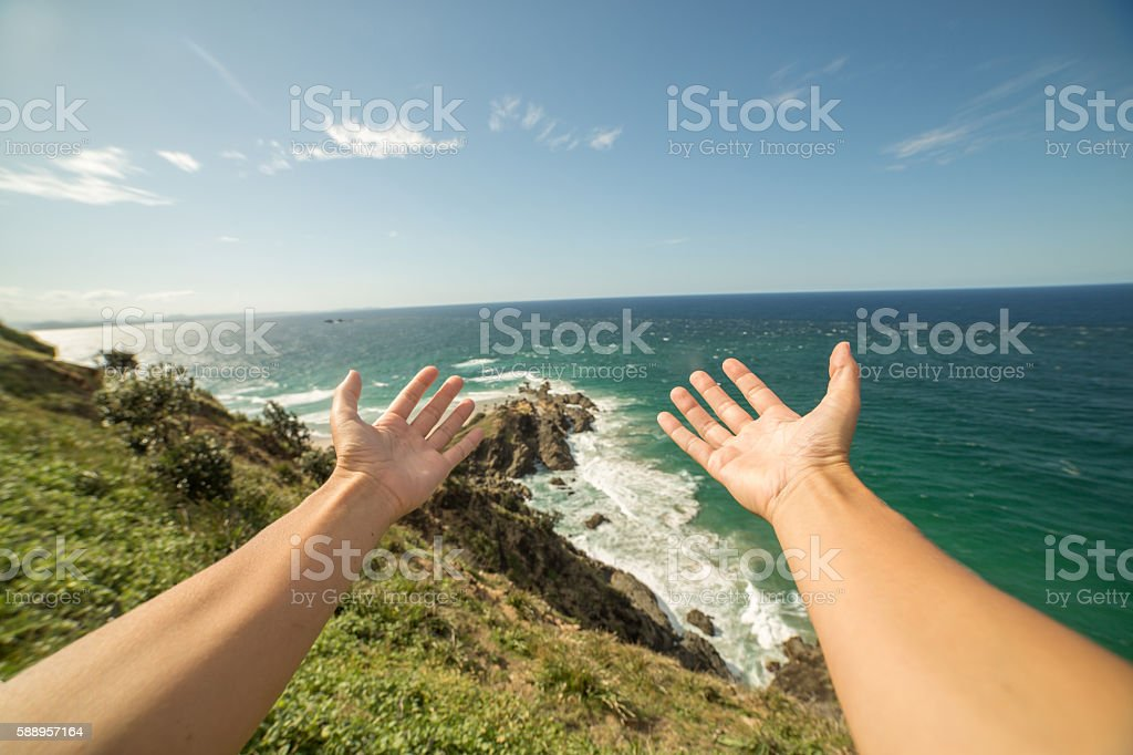 Woman's arms stretch towards Cape Byron stock photo