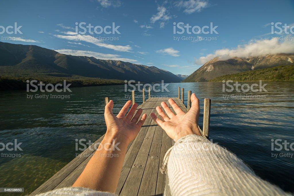 Woman's arms stretch towards mountain lake stock photo