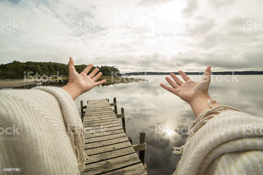 Woman's arms stretch towards mountain lake, success concept stock photo