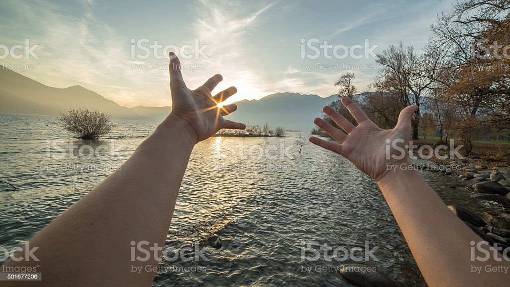 Woman's arms stretch towards sun setting over mountains stock photo