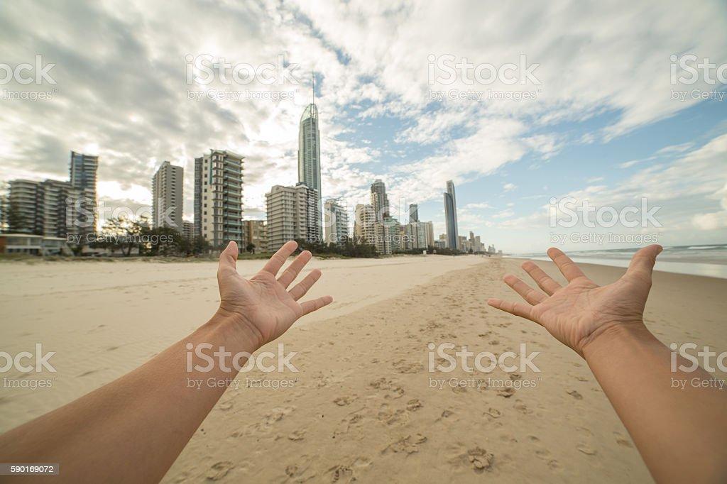 Woman's arms stretch towards Surfer's Paradise skyline stock photo