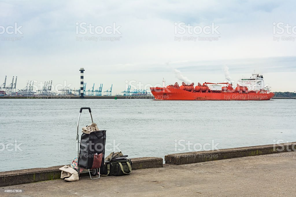 womans baggage in the Rotterdam harbor with orange chemical tanker stock photo