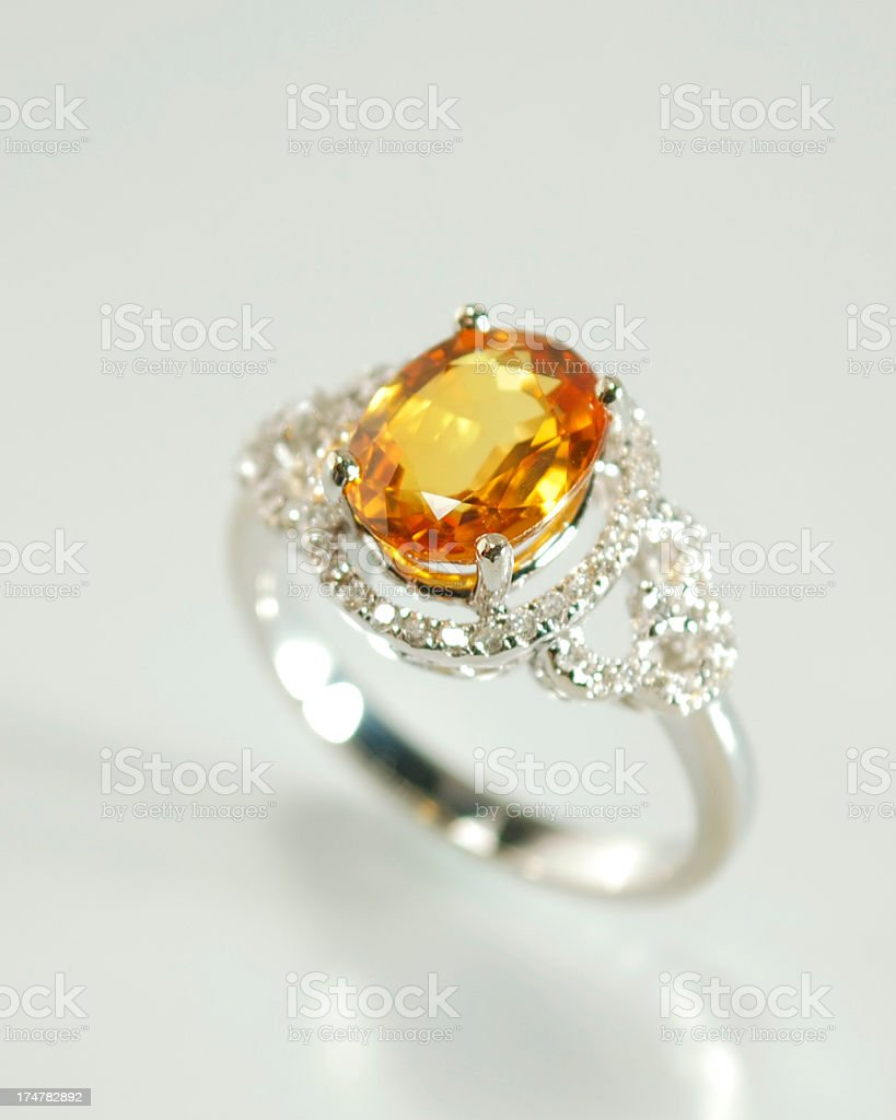 Woman's Diamond, Orange Sapphire and Gold Ring royalty-free stock photo