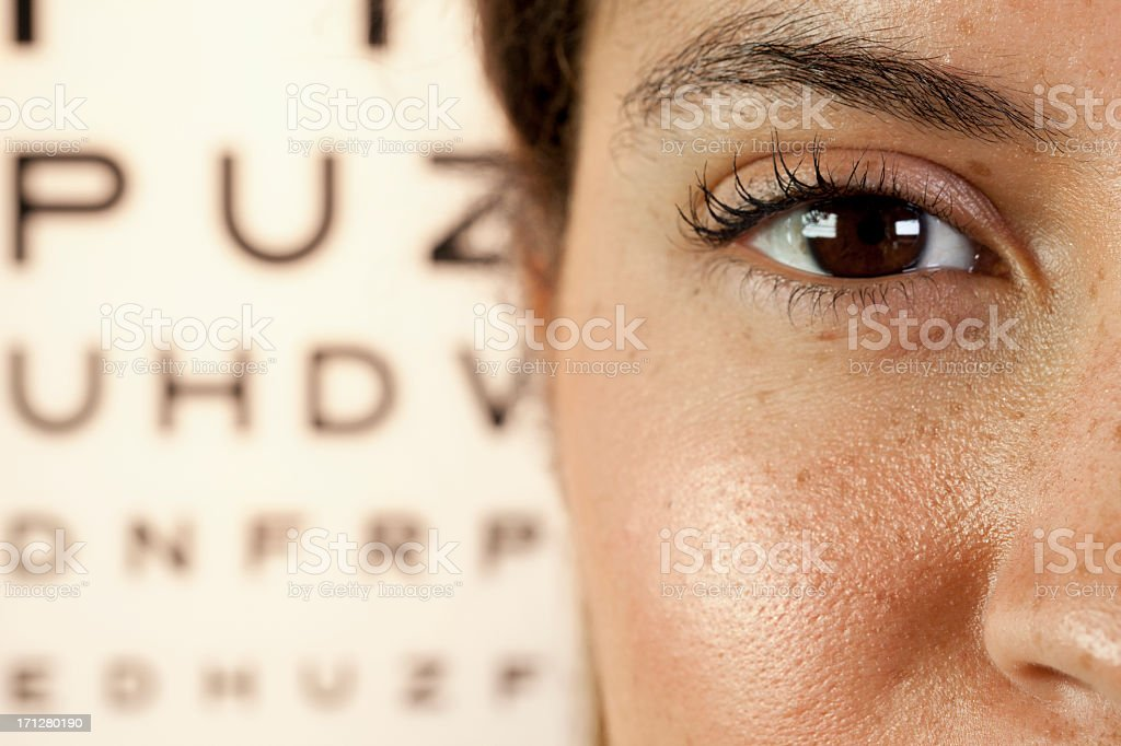 Woman's eye close-up with an eye test in the background stock photo