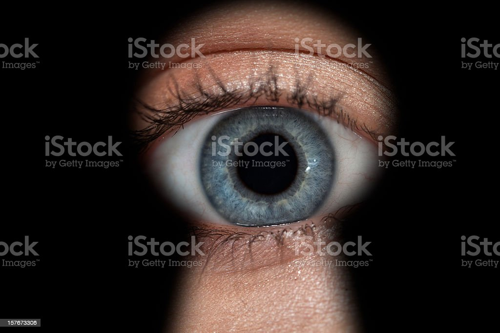 Woman's eye in keyhole stock photo
