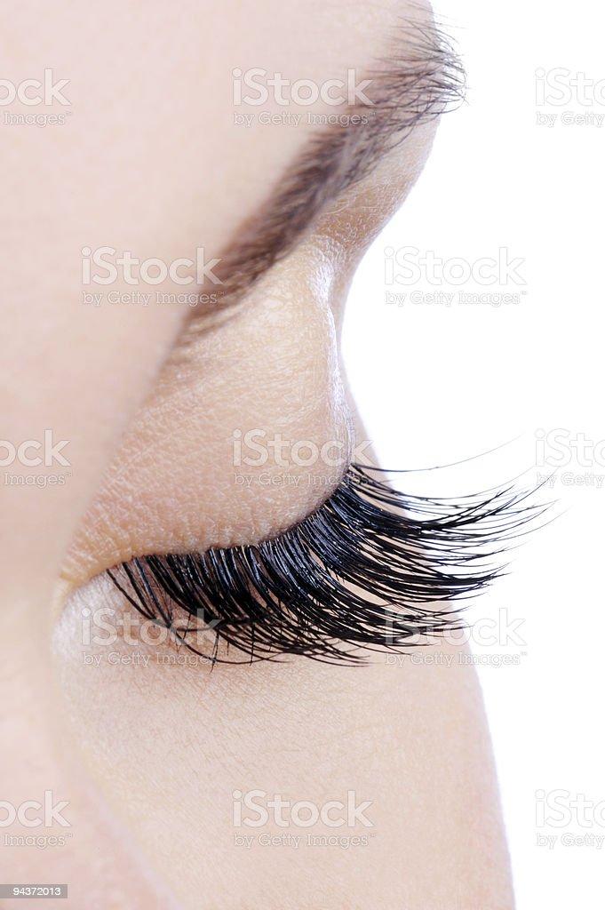 Woman's eye with long, dark false eyelashes stock photo