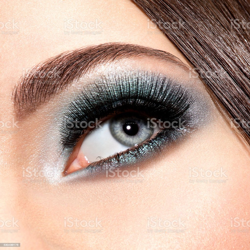 woman's eye with turquoise makeup. Long false eyelashes. macro stock photo