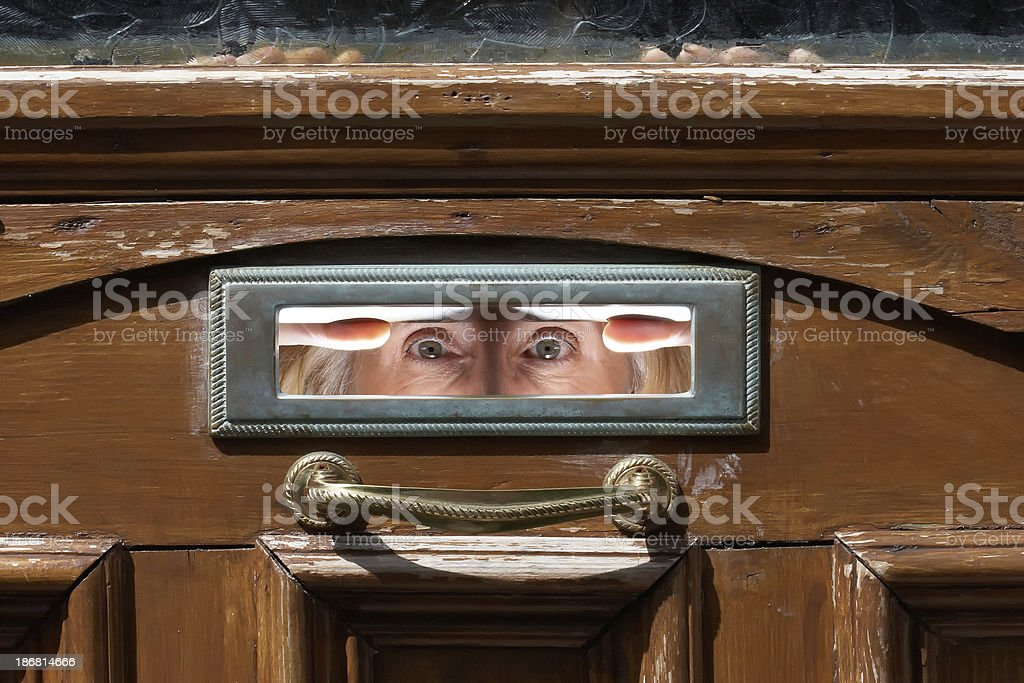 Woman's eyes peering out from letterbox stock photo