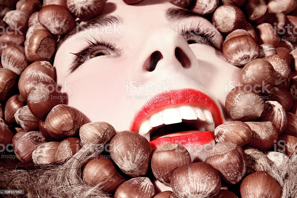 Woman's Face Surrounded by Hazelnuts stock photo